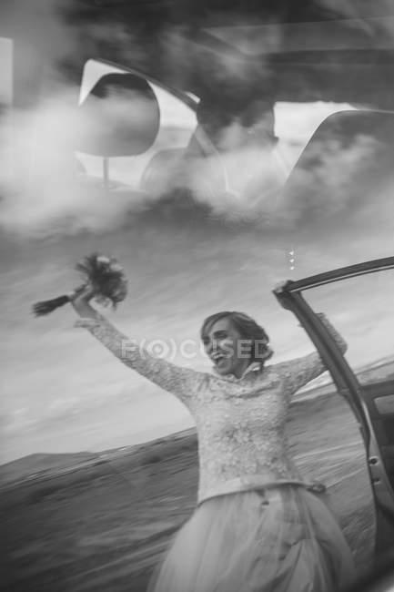Feliz novia sosteniendo ramo y novio coche de conducción - foto de stock