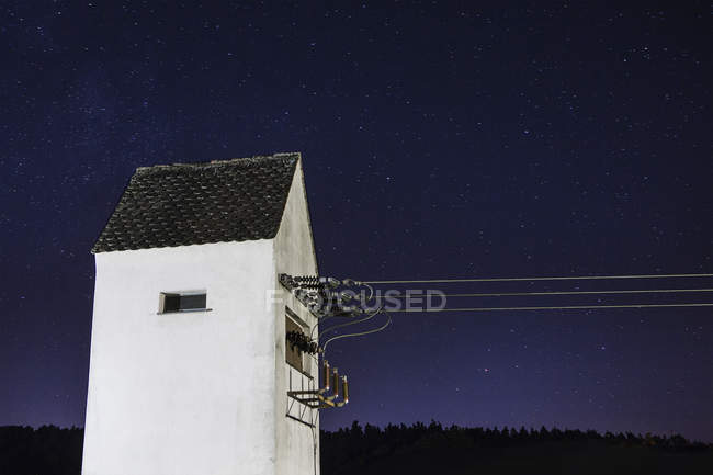 Power cables attached to building against starry sky — Stock Photo