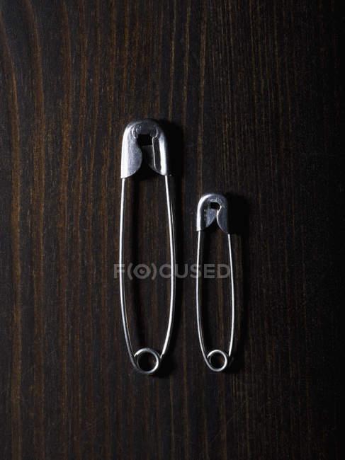 Dessus vue de différentes tailles épingles de sûreté sur la table en bois — Photo de stock