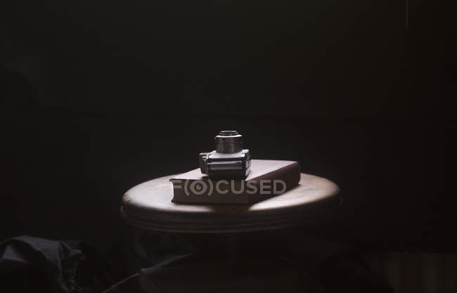 Still life of camera and book on table against black background — Stock Photo