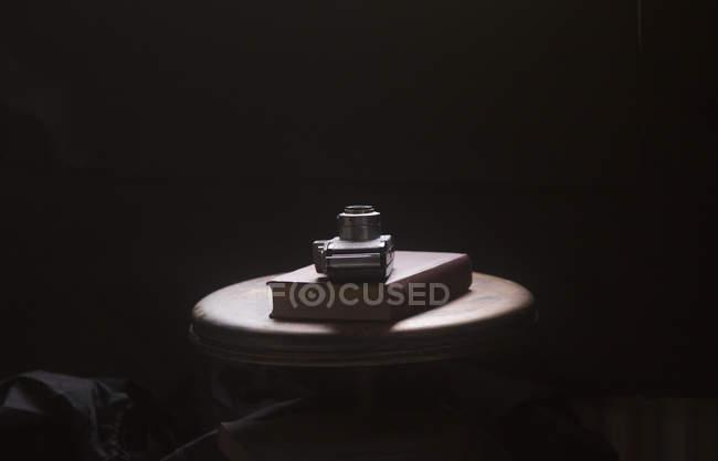 Натюрморт камеры и книги на столе черном фоне — стоковое фото