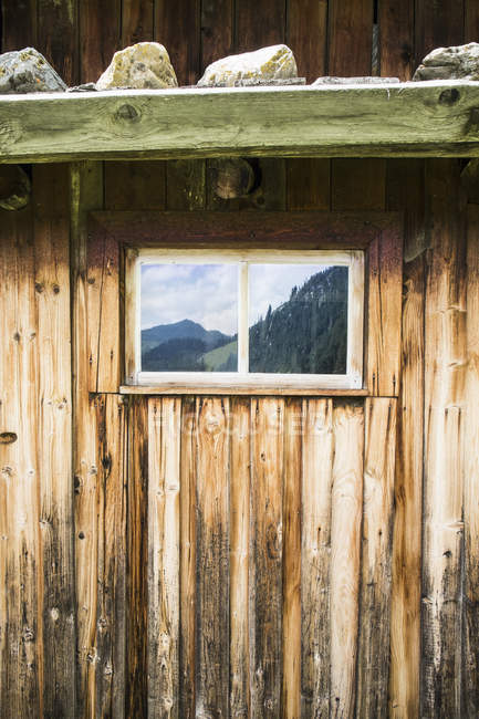 Full frame shot of log cabin with reflection of mountains on window — Stock Photo
