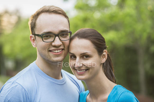 Portrait of young couple smiling together in park — Stock Photo
