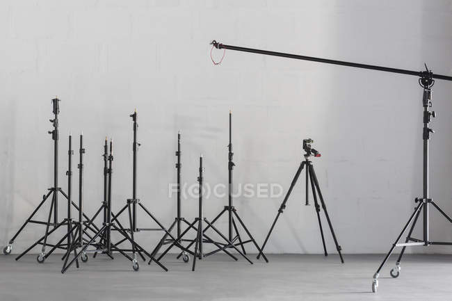 Rows of tripods by wall at photography studio — Stock Photo