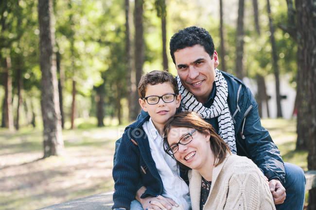 Портрет счастливой семьи сидящей в лесу — стоковое фото