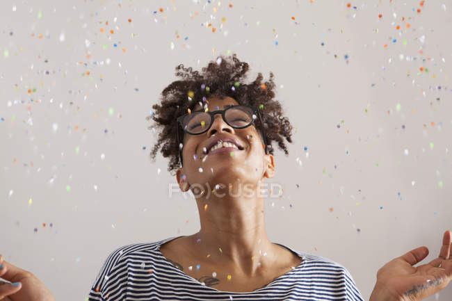 Happy young woman with confetti falling on gray background — Stock Photo