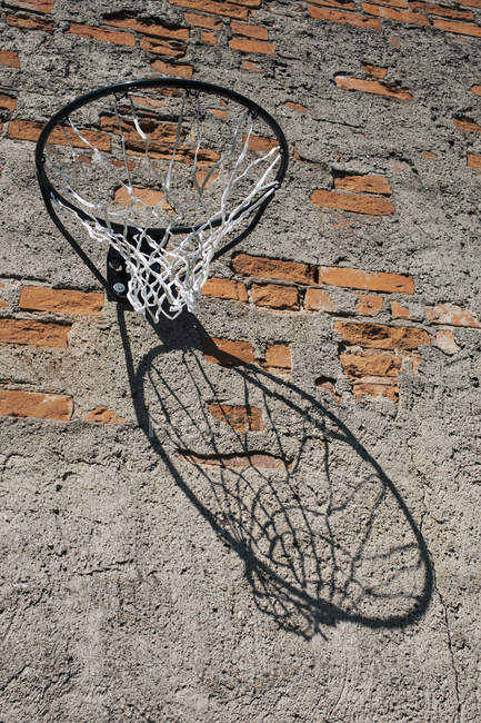 Vista de ângulo baixo da cesta de basquete, montada na parede de tijolos gasto — Fotografia de Stock