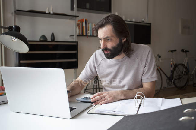 Focused man working on laptop at home — Stock Photo