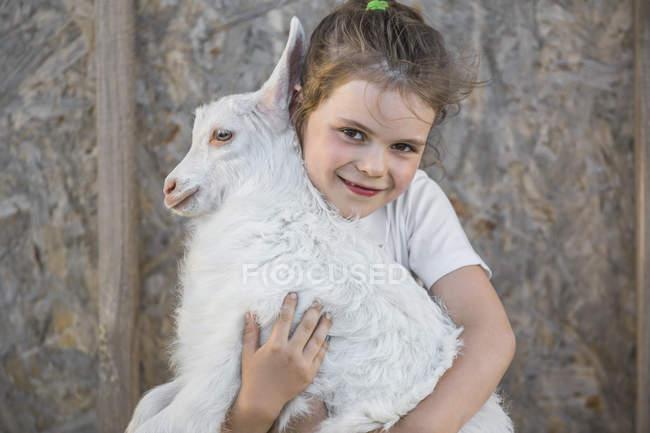 Portrait de fille mignonne tenant bébé chèvre en plein air — Photo de stock
