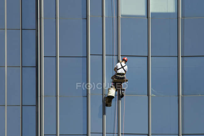 Rear view of worker washing windows of office building — Stock Photo
