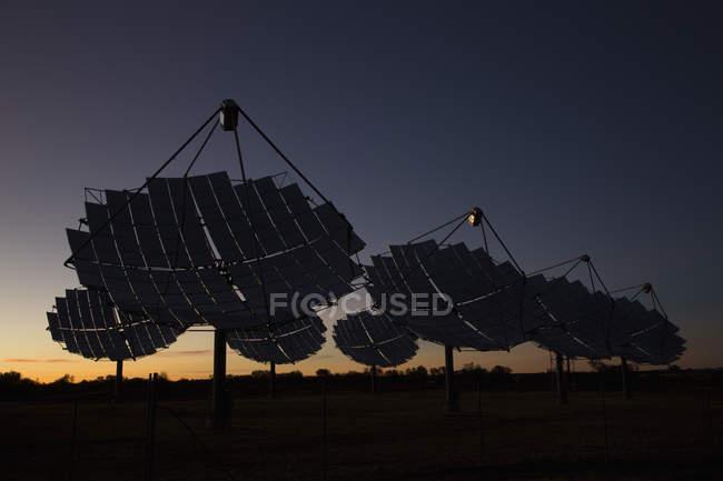 Солнечные блюда на электростанции против неба на закате — стоковое фото