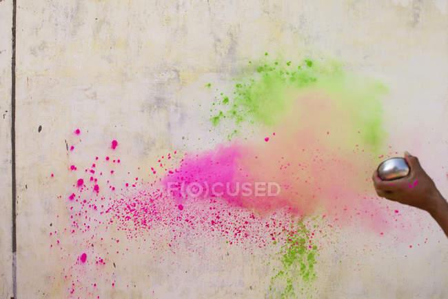 Рука культур, бросали порошок краски на стену — стоковое фото