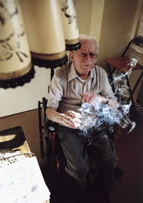 Senior man in a wheelchair smoking a cigarette — Stock Photo