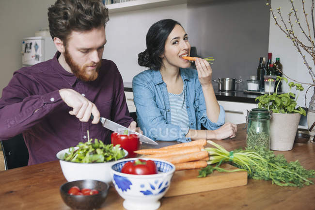 Young man chopping red bell pepper beside woman eating carrot at kitchen table — Stock Photo