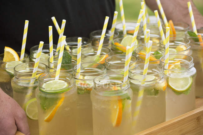 Crop person carrying lemonade in mason jars with drinking straws on tray — Stock Photo