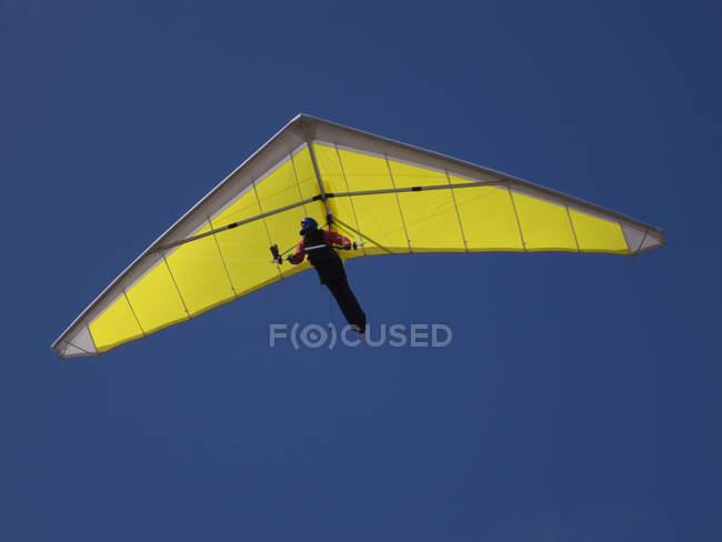 Vista di angolo basso di persona deltaplano contro cielo azzurro chiaro — Foto stock