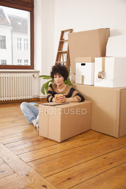 Portrait of serious woman taking coffee break while moving house — Stock Photo