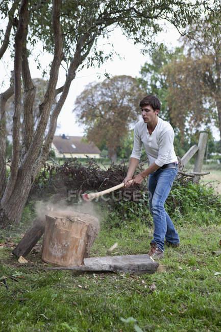 Homme coupant du bois de chauffage avec hache à la campagne — Photo de stock