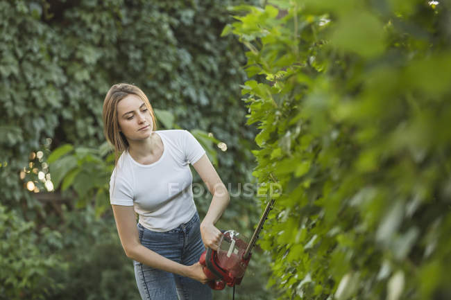 Young woman cutting plants with hedge clipper at yard — Stock Photo