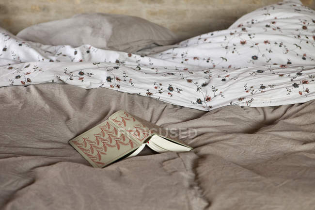 Still life of open book on bed at home — Stock Photo