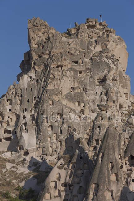 Скальное образование с пещерами против ясного голубого неба. — стоковое фото