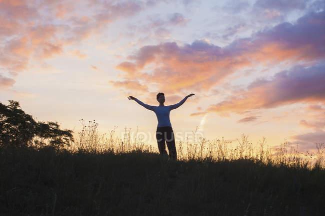 Жінка, стоячи з руки розкритими на травою поле проти заходу сонця небо — стокове фото