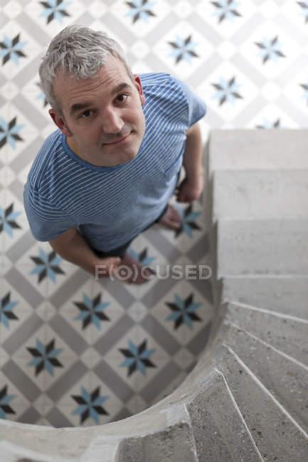 Homme souriant, debout sur le plancher à motifs en forme d'étoile — Photo de stock