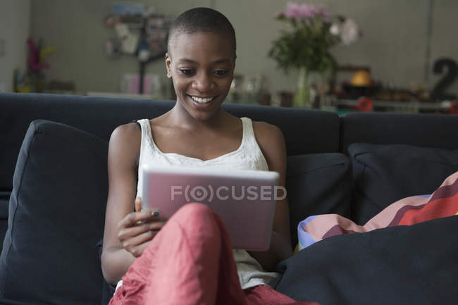 Smiling young woman using digital tablet on sofa at home — Stock Photo