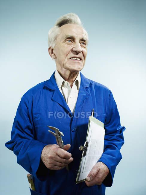 Fröhlicher Senior in Overalls mit Klemmbrett und Arbeitsgerät — Stockfoto