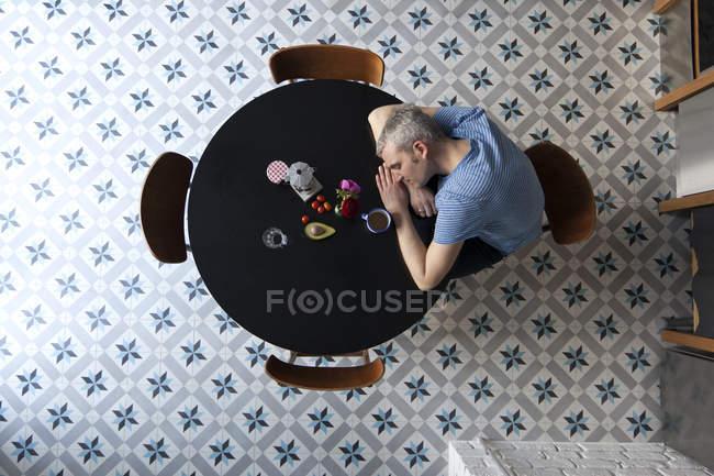 Homem cansado com a cabeça descansando nos braços, sentado à mesa — Fotografia de Stock