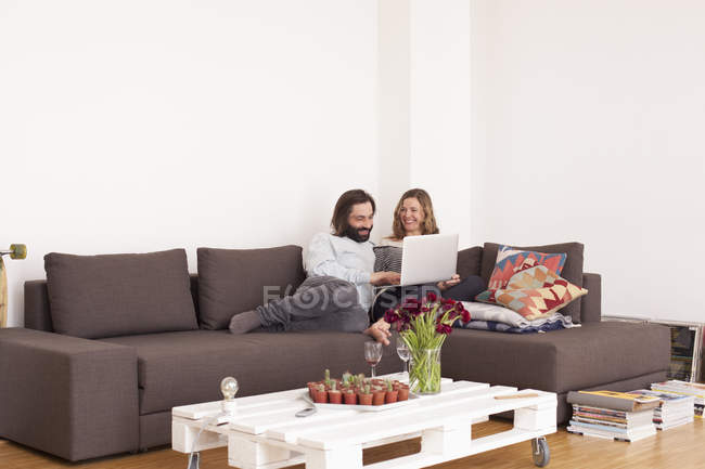 Mid adult couple using laptop in living room — Stock Photo