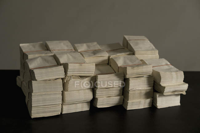 Stack of white  envelopes on table against wall — Stock Photo