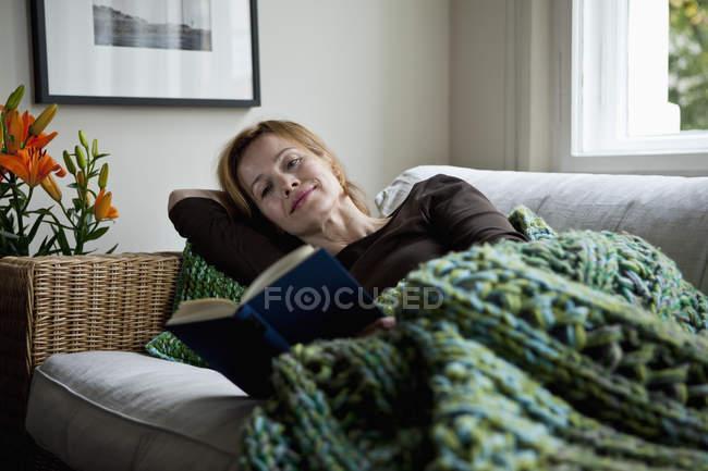 Frau liest Buch, während sie zu Hause auf Sofa liegt — Stockfoto