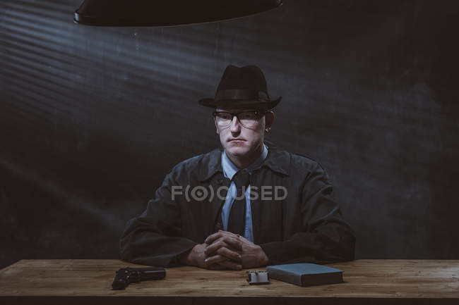 Portrait of young man sitting at table with gun against black wall — Stock Photo