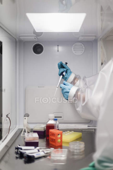 Cropped image of scientist holding pipette over machinery at laboratory — Stock Photo
