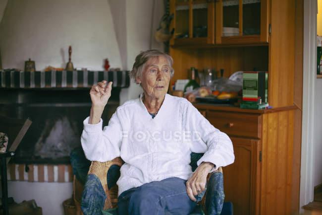 Nachdenklich senior Frau sitzend auf Sessel zu Hause wegschauen — Stockfoto