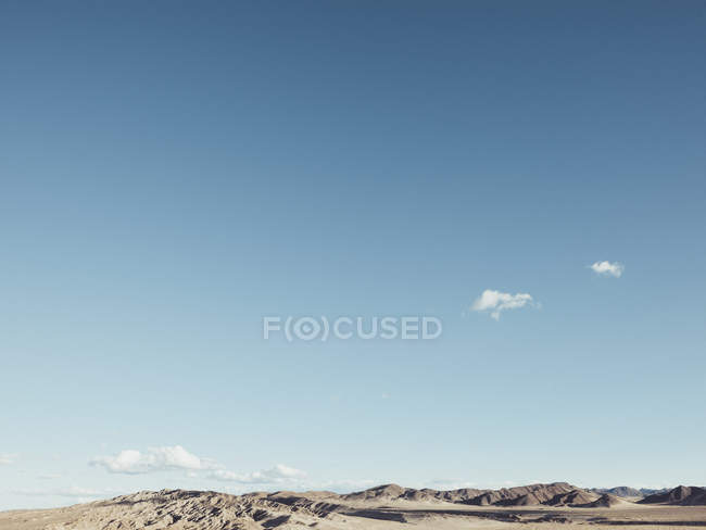 Scenic view of desert landscape with hills against blue sky — Stock Photo
