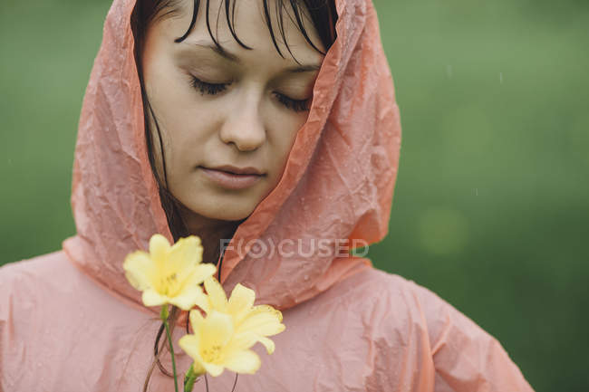 Close-up of woman wearing raincoat holding yellow flowers in rainy season — Stock Photo
