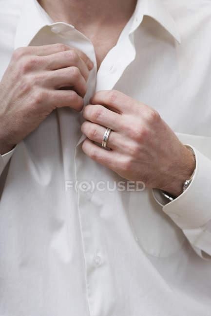 Животик человек расстегивающем белая рубашка — стоковое фото