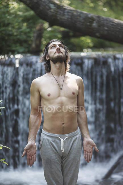 Hemdloser junger Mann blickt auf, während er gegen Wasserfall im Wald steht — Stockfoto