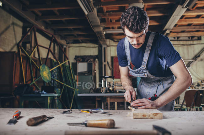 Carpenter using chisel on plank of wood in workshop — Stock Photo