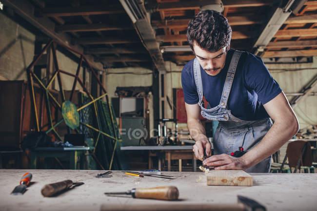 Charpentier utilisant le ciseau sur la planche de bois en atelier — Photo de stock