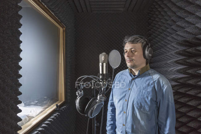 Musician standing by microphone with headphones in recording studio — Stock Photo