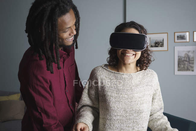 Happy man looking at woman using virtual reality headset in living room — Stock Photo
