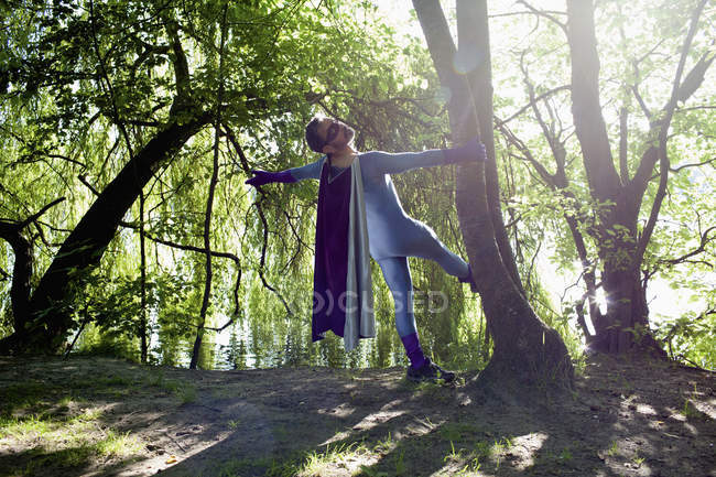 Male superhero standing in forest at riverbank on sunny day — Stock Photo
