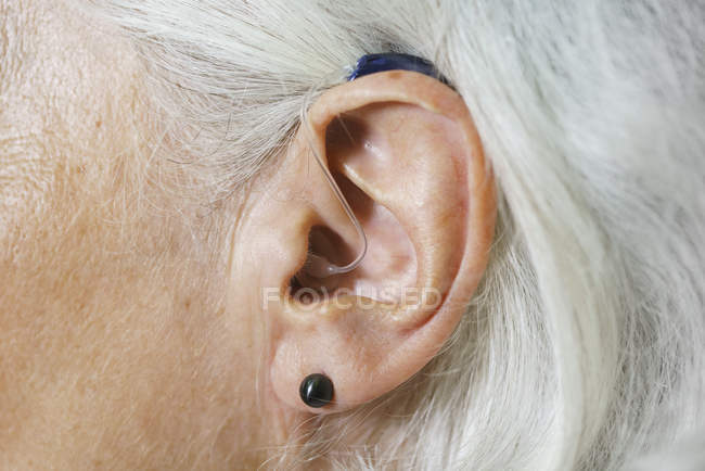 Crop woman with gray hair wearing hearing aid — Stock Photo