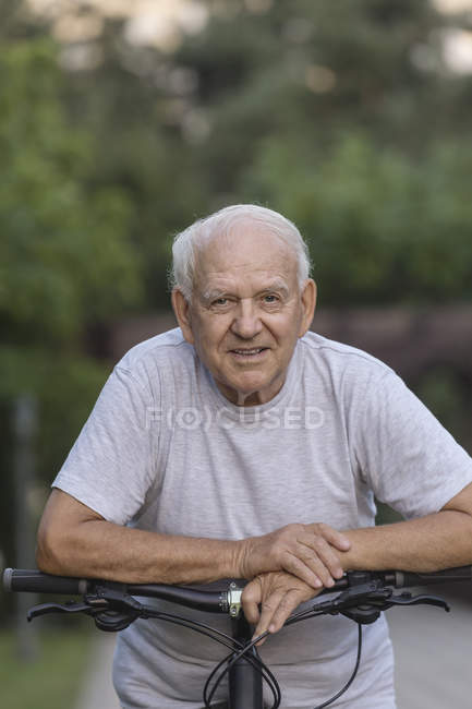 Portrait of senior man leaning on bicycle in park — Stock Photo