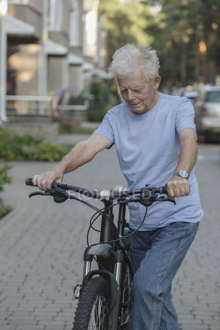 Senior homem de bicicleta na rua de paralelepípedos na cidade — Fotografia de Stock