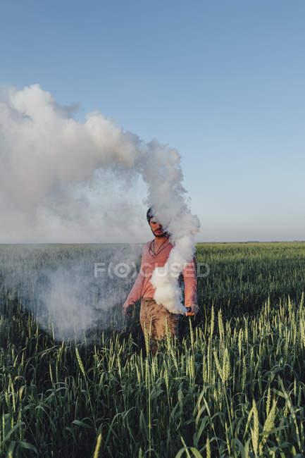Homme debout avec fusée de détresse dégageant de la fumée sur le terrain contre le ciel bleu — Photo de stock