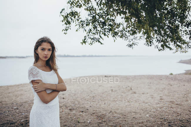Portrait Of Teenage Girl Standing With Arms Crossed At Lake
